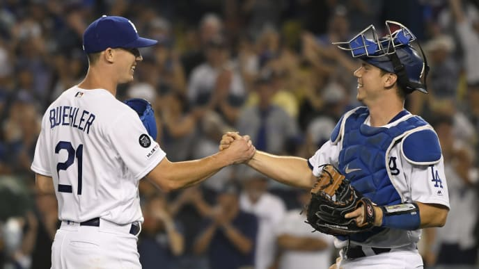 LOS ANGELES, CA - AUGUST 03: Walker Buehler #21 of the Los Angeles Dodgers is congratulated by Will Smith #16 of the Los Angeles Dodgers after his complete game victory over the San Diego Padres at Dodger Stadium on August 3, 2019 in Los Angeles, California. Dodgers won 4-1. (Photo by John McCoy/Getty Images)