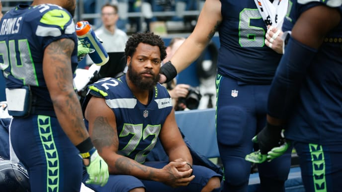 SEATTLE, WA - SEPTEMBER 17: Running back Thomas Rawls #34 of the Seattle Seahawks stands with center Justin Britt #68, right, to join defensive end Michael Bennett #72 on the bench during the national anthem before the game at CenturyLink Field on September 17, 2017 in Seattle, Washington. (Photo by Otto Greule Jr /Getty Images)