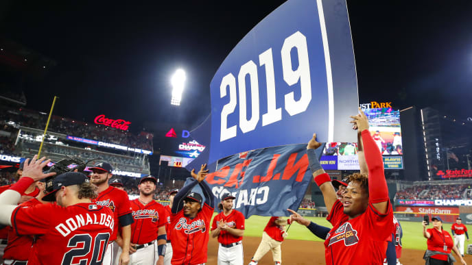 ATLANTA, GA - SEP 20: Ozzie Albies #1 of the Atlanta Braves and Ronald Acuna Jr. #13 hold up a 2019 banner at the conclusion of an MLB game against the San Francisco Giants in which they clinched the NL East at SunTrust Park on September 20, 2019 in Atlanta, Georgia. (Photo by Todd Kirkland/Getty Images)