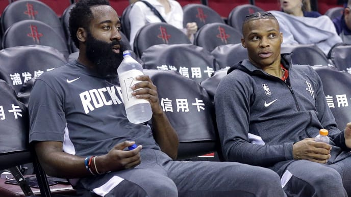 HOUSTON, TEXAS - SEPTEMBER 30: James Harden #13 of the Houston Rockets, left, and Russell Westbrook #0 sit in the bench during warmups  before playing a pre-season game against the Shanghai Sharks at Toyota Center on September 30, 2019 in Houston, Texas. NOTE TO USER: User expressly acknowledges and agrees that, by downloading and/or using this photograph, user is consenting to the terms and conditions of the Getty Images License Agreement.  (Photo by Bob Levey/Getty Images)