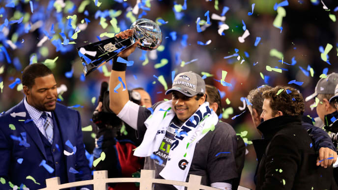 EAST RUTHERFORD, NJ - FEBRUARY 02:  Russell Wilson #3 of the Seattle Seahawks celebrates with the Vince Lombardi trophy after defeating the Denver Broncos 43-8 in Super Bowl XLVIII at MetLife Stadium on February 2, 2014 in East Rutherford, New Jersey.  (Photo by Rob Carr/Getty Images)