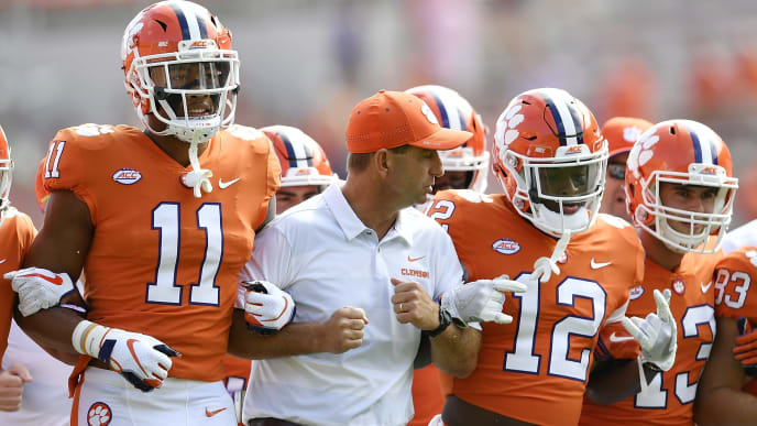 CLEMSON, SC - SEPTEMBER 29: Head coach Dabo Swinney links arms with safety Isaiah Simmons #11 and defensive back K'Von Wallace #12 of the Clemson Tigers during Tigers' traditional Face Off prior to their football game against the Syracuse Orange at Clemson Memorial Stadium on September 29, 2018 in Clemson, South Carolina. (Photo by Mike Comer/Getty Images)