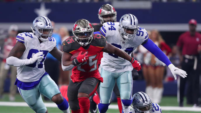 ARLINGTON, TEXAS - DECEMBER 23: Peyton Barber #25 of the Tampa Bay Buccaneers breaks away from Taco Charlton #97, Randy Gregory #94, and #25 of the Dallas Cowboys in the third quarter at AT&T Stadium on December 23, 2018 in Arlington, Texas. (Photo by Tom Pennington/Getty Images)