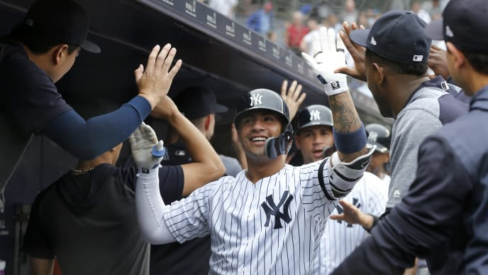 NEW YORK, NEW YORK - JUNE 19:   Gleyber Torres #25 of the New York Yankees celebrates his seventh inning grand slam home run against the Tampa Bay Rays in the dugout with his teammates at Yankee Stadium on June 19, 2019 in New York City. (Photo by Jim McIsaac/Getty Images)