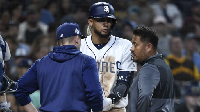 SAN DIEGO, CA - AUGUST 13: Andy Green #14 of the San Diego Padres and a trainer talk with Fernando Tatis Jr. #23 during the  sixth inning of a baseball game against the Tampa Bay Rays at Petco Park August 13, 2019 in San Diego, California.  (Photo by Denis Poroy/Getty Images)