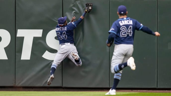 SEATTLE, WA - AUGUST 11: Centerfielder Guillermo Heredia #54 of the Tampa Bay Rays hits the wall as he makes a catch on a ball hit by Austin Nola #23 of the Seattle Mariners during the seventh inning of a game at T-Mobile Park on August 11, 2019 in Seattle, Washington. At right, rightfielder Avisail Garcia #24 of the Tampa Bay Rays. (Photo by Stephen Brashear/Getty Images)