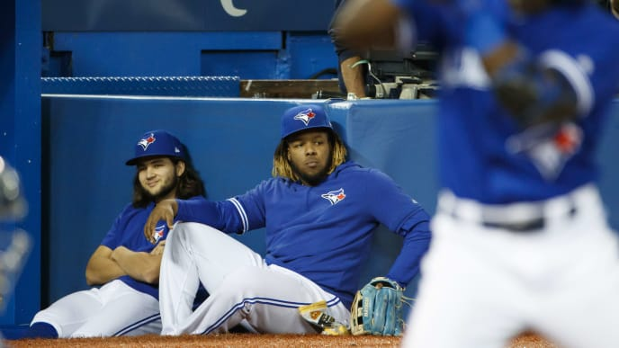 TORONTO, ON - SEPTEMBER 28: Bo Bichette #11 and Vladimir Guerrero Jr. #27 of the Toronto Blue Jays sit in the dugout as Jonathan Davis #49 of the Toronto Blue Jays takes an at bat during the eighth inning of their MLB game against the Tampa Bay Rays at Rogers Centre on September 28, 2019 in Toronto, Canada. (Photo by Cole Burston/Getty Images)