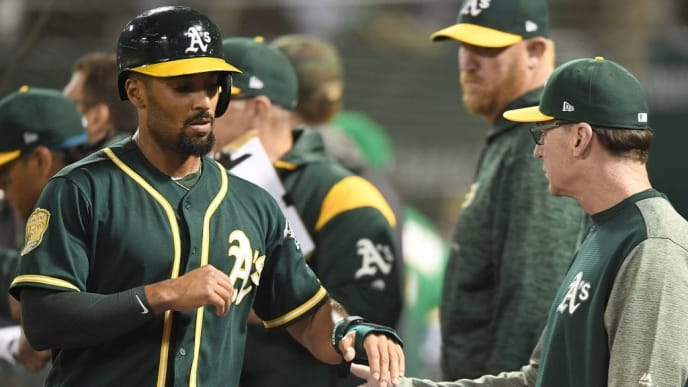 OAKLAND, CA - AUGUST 21:  Marcus Semien #10 of the Oakland Athletics is congratulated by manager Bob Melvin #6 after Semien scored against the Texas Rangers in the bottom of the six inning at Oakland Alameda Coliseum on August 21, 2018 in Oakland, California.  (Photo by Thearon W. Henderson/Getty Images)