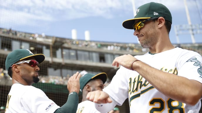 OAKLAND, CA - SEPTEMBER 22: Matt Olson #28 of the Oakland Athletics high-fives teammate Marcus Semien #10 before their game against the Texas Rangers at Ring Central Coliseum on September 22, 2019 in Oakland, California. (Photo by Stephen Lam/Getty Images)