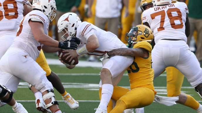 WACO, TEXAS - NOVEMBER 23:  Sam Ehlinger #11 of the Texas Longhorns is sacked by Terrel Bernard #26 of the Baylor Bears in the first half at McLane Stadium on November 23, 2019 in Waco, Texas. (Photo by Ronald Martinez/Getty Images)