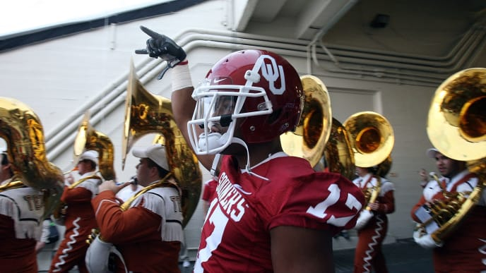"DALLAS - OCTOBER 11:  Running back Mossis Madu #17 of the Oklahoma Sooners gives a downward ""hook em horns"" sign while walking to the field alongside the Texas Longhorns band at the Cotton Bowl on October 11, 2008 in Dallas, Texas.  (Photo by Ronald Martinez/Getty Images)"