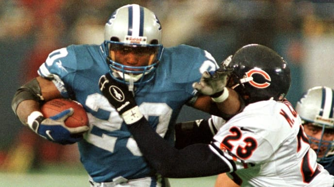 PONTIAC, :  The Detroit Lions' Barry Sanders (L) brushes off Chicago Bears safety Marty Carter (R) on his way to the end zone for a touchdown in the third quarter, 27 November, at the Silverdome in Pontiac, MI.  On the play, Sanders passed the 100-yard mark in a game for the 11th straight time tieing the NFL record held by Marcus Allen. The Lions beat the Bears 55-20. AFP PHOTO Matt CAMPBELL (Photo credit should read MATT CAMPBELL/AFP via Getty Images)