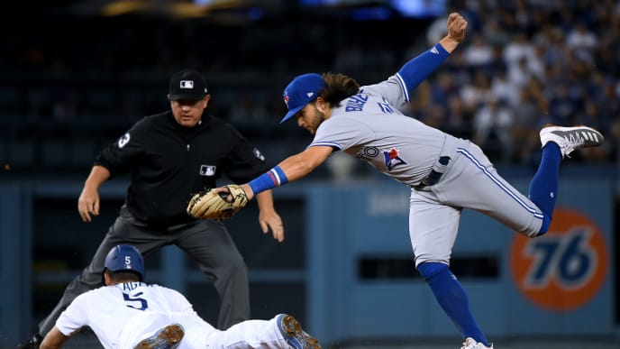 LOS ANGELES, CALIFORNIA - AUGUST 21:  Bo Bichette #11 of the Toronto Blue Jays stretches for a throw, as Corey Seager #5 of the Los Angeles Dodgers slides in to second base with a double, during the second inning at Dodger Stadium on August 21, 2019 in Los Angeles, California. (Photo by Harry How/Getty Images)
