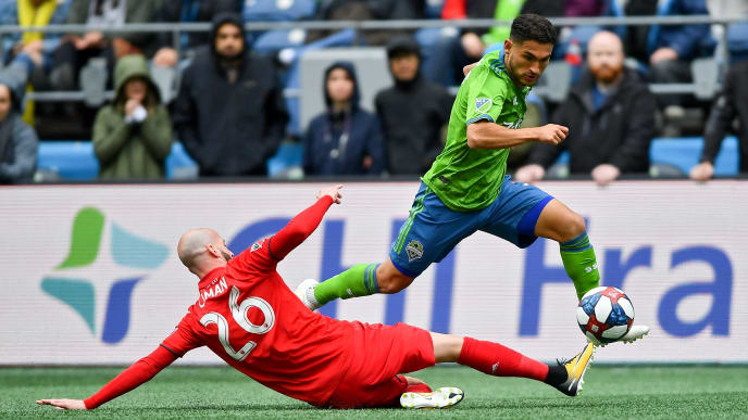 SEATTLE, WASHINGTON - APRIL 13: Cristian Roldan #7 of Seattle Sounders makes a move against Laurent Ciman #26 of Toronto FC during the match at CenturyLink Field on April 13, 2019 in Seattle, Washington. The Seattle Sounders beat the Toronto FC 3-2. (Photo by Alika Jenner/Getty Images)