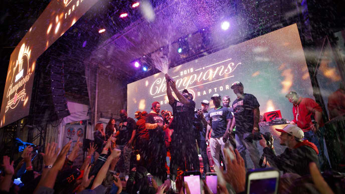 TORONTO, ON - JUNE 13: Toronto rapper Drake sprays the crowd with champaign as Toronto Raptors beat the Golden State Warriors in Game Six of the NBA Finals, during a viewing party in Jurassic Park outside of Scotiabank Arena on June 13, 2019 in Toronto, Canada. (Photo by Cole Burston/Getty Images)