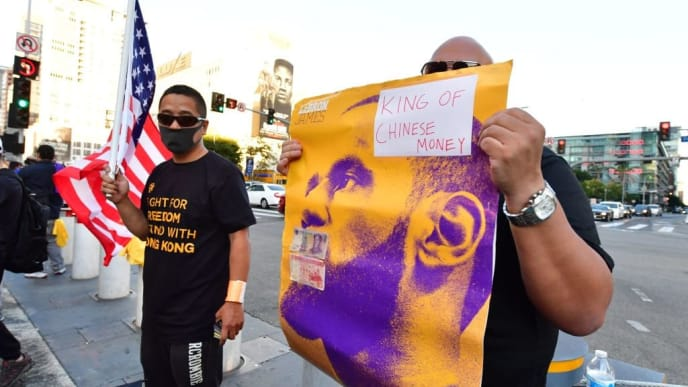 """Hong Kong supportes hold signs outside the Staples center ahead of the Lakers vs Clippers NBA season opener in Los Angeles on October 22, 2019. - Activists plan to hand out free T-shirts displaying support for the Hong Kong protests. A GoFundMe fundraiser """"Give Away Hong Kong T-Shirts, NBA Opening Night"""" set up on October 7 by an NBA fan in Northern California, raised enough money to pay for more than 10,000 shirts, according to the organizer who goes by the pseudonym """"Sun Lared."""" (Photo by Frederic J. BROWN / AFP) (Photo by FREDERIC J. BROWN/AFP via Getty Images)"""