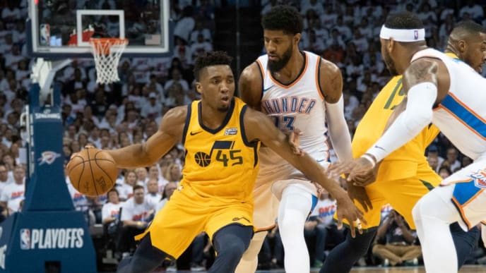 OKLAHOMA CITY, OK - APRIL 18:  Donovan Mitchell #45 of the Utah Jazz battles his way around Paul George #13 of the Oklahoma City Thunder during the first half of Game 2 of the Western Conference playoffs at the Chesapeake Energy Arena on April 18, 2018 in Oklahoma City, Oklahoma. NOTE TO USER: User expressly acknowledges and agrees that, by downloading and or using this photograph, User is consenting to the terms and conditions of the Getty Images License Agreement. (Photo by J Pat Carter/Getty Images)
