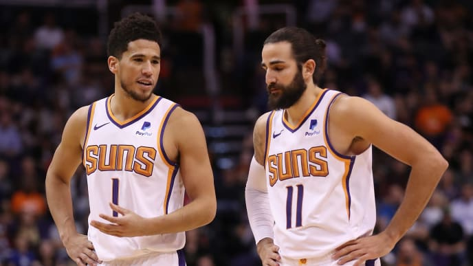 PHOENIX, ARIZONA - OCTOBER 28: Devin Booker #1 of the Phoenix Suns talks with Ricky Rubio #11 during the second half of the NBA game against the Utah Jazz at Talking Stick Resort Arena on October 28, 2019 in Phoenix, Arizona. The Jazz defeated the Suns 96-95. NOTE TO USER: User expressly acknowledges and agrees that, by downloading and/or using this photograph, user is consenting to the terms and conditions of the Getty Images License Agreement  (Photo by Christian Petersen/Getty Images)