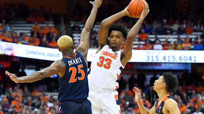 SYRACUSE, NY - NOVEMBER 06:  Elijah Hughes #33 of the Syracuse Orange looks to pass the ball between Mamadi Diakite #25 and Kihei Clark #0 of the Virginia Cavaliers during the second half at the Carrier Dome on November 6, 2019 in Syracuse, New York. Virginia defeated Syracuse 48-34. (Photo by Rich Barnes/Getty Images)