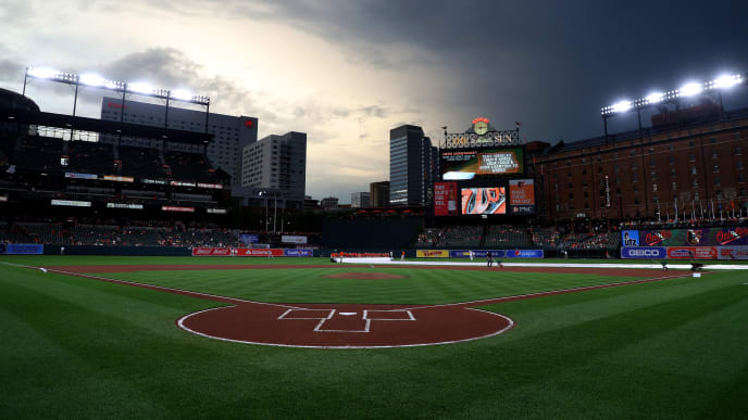 BALTIMORE, MARYLAND - JULY 17: The grounds crew removes the tarp before the start of the rained delayed Washington Nationals and Baltimore Orioles game at Oriole Park at Camden Yards on July 17, 2019 in Baltimore, Maryland. (Photo by Rob Carr/Getty Images)