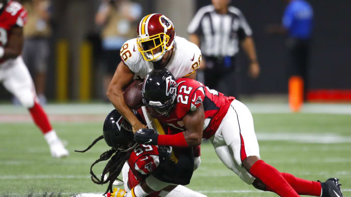 ATLANTA, GA - AUGUST 22: Tight end Jordan Reed #86 of the Washington Redskins is hit and loses his helmet by outside linebacker De'Vondre Campbell #59 of the Atlanta Falcons and strong safety Keanu Neal #22 in the first half of an NFL preseason game at Mercedes-Benz Stadium on August 22, 2019 in Atlanta, Georgia. (Photo by Todd Kirkland/Getty Images)