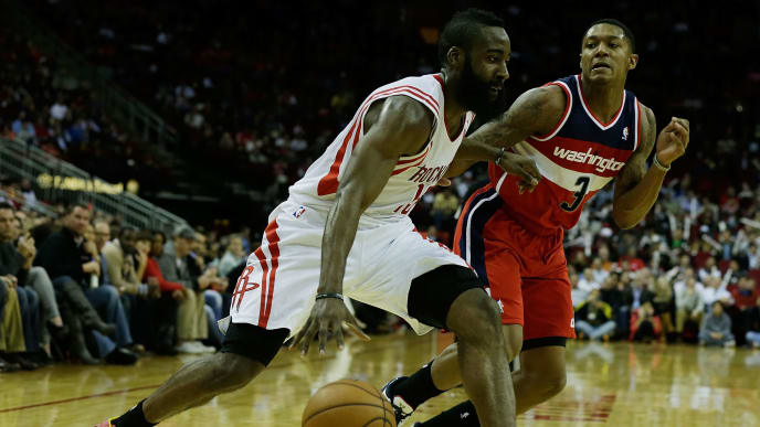 HOUSTON, TX - DECEMBER 12:  James Harden #13 of the Houston Rockets drives past Bradley Beal #3 of the Washington Wizards at the Toyota Center on December 12, 2012 in Houston, Texas. NOTE TO USER: User expressly acknowledges and agrees that, by downloading and or using this photograph, User is consenting to the terms and conditions of the Getty Images License Agreement.  (Photo by Scott Halleran/Getty Images)