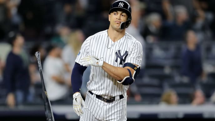 NEW YORK, NEW YORK - OCTOBER 03:  Giancarlo Stanton #27 of the New York Yankees celebrates after scoring a solo home run against the Oakland Athletics during the eighth inning in the American League Wild Card Game at Yankee Stadium on October 03, 2018 in the Bronx borough of New York City. (Photo by Elsa/Getty Images)