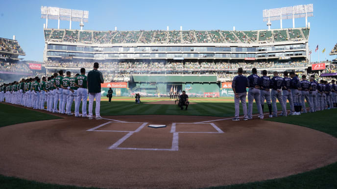 OAKLAND, CALIFORNIA - OCTOBER 02: The Oakland Athletics and the Tampa Bay Rays stand during the national anthem prior to the American League Wild Card Game at RingCentral Coliseum on October 02, 2019 in Oakland, California. (Photo by Thearon W. Henderson/Getty Images)
