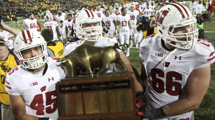 IOWA CITY, IOWA- SEPTEMBER 22:  Fullback Alec Ingold #45, offensive lineman Michael Dieter #63 and offensive lineman Tyler Beach #65 of the Wisconsin Badgers carry the Heartland Trophy off the field after defeating the Iowa Hawkeyes, on September 22, 2018 at Kinnick Stadium, in Iowa City, Iowa.  (Photo by Matthew Holst/Getty Images)