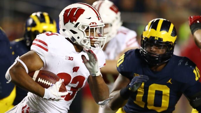 ANN ARBOR, MI - OCTOBER 13: Jonathan Taylor #23 of the Wisconsin Badgers tries to outrun the tackle of Devin Bush #10 of the Michigan Wolverines during the second half on October 13, 2018 at Michigan Stadium in Ann Arbor, Michigan. Michigan won the game 38-13. (Photo by Gregory Shamus/Getty Images)
