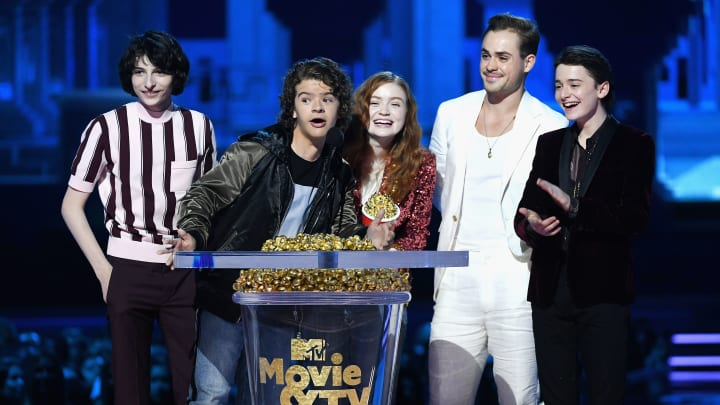 SANTA MONICA, CA - JUNE 16:  (L-R) Actors Finn Wolfhard, Gaten Matarazzo, Sadie Sink, Dacre Montgomery, and Noah Schnapp accept the Best Show award for 'Stranger Things' onstage during the 2018 MTV Movie And TV Awards at Barker Hangar on June 16, 2018 in Santa Monica, California.  (Photo by Kevin Winter/Getty Images for MTV)