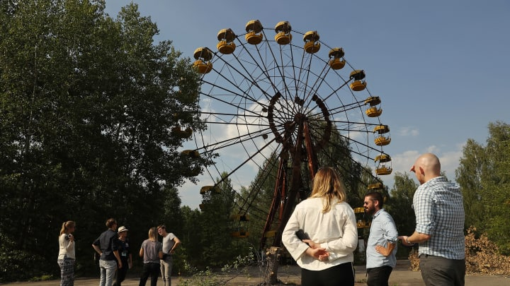 PRIPYAT, UKRAINE - AUGUST 19:  Tourists look at an abandoned ferris wheel in the ghost town of Pripyat not far from the Chernobyl nuclear power plant on August 19, 2017 in Pripyat, Ukraine. On April 26, 1986 reactor number four exploded after a safety test went wrong, spreading radiation over thousands of square kilometers in different directions. Ukraine and Belarus are still challenged by the consequences of the accident, with huge swaths of territory that remain uninhabitable as well as ongoing health effects for their populations.  (Photo by Sean Gallup/Getty Images)