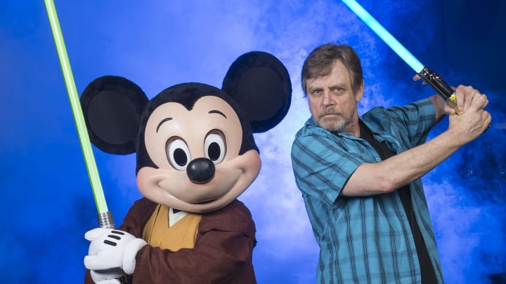 "LAKE BUENA VISTA, FL - JUNE 05:  In this handout photo provided by Disney Parks, actor Mark Hamill, who portrayed Luke Skywalker in the 'Star Wars' film saga, poses with Jedi Mickey Mouse at Disney's Hollywood Studios June 5, 2014 in Lake Buena Vista, Florida.  Hamill is at the Walt Disney World Resort theme park for appearances June 6-8 at ""Star Wars Weekends,"" an annual special event.  This year marks the first time Hamill has attended 'Star Wars Weekends' in the event's 17-year history.  (Photo by David Roark/Disney Parks via Getty Images)"