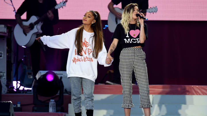 MANCHESTER, ENGLAND - JUNE 04:  NO SALES, free for editorial use. In this handout provided by 'One Love Manchester' benefit concert (L) Ariana Grande and Miley Cyrus perform on stage on June 4, 2017 in Manchester, England. Donate at www.redcross.org.uk/love  (Photo by Getty Images/Dave Hogan for One Love Manchester)