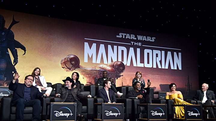 "HOLLYWOOD, CALIFORNIA - NOVEMBER 13: (L-R) Executive Producer Jon Favreau, Composer Ludwig Göransson, Executive Producer/Director Dave Filoni, Director Deborah Chow, Pedro Pascal, Rick Famuyiwa, Carl Weathers, Director Bryce Dallas Howard, Gina Carano and Werner Herzog speak onstage at the premiere of Lucasfilm's first-ever, live-action series, ""The Mandalorian,"" at the El Capitan Theatre in Hollywood, Calif. on November 13, 2019. ""The Mandalorian"" streams exclusively on Disney+.  (Photo by Alberto E. Rodriguez/Getty Images for Disney)"