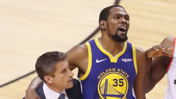 TORONTO, ONTARIO - JUNE 10:  Kevin Durant #35 of the Golden State Warriors is assisted off the court after sustaining an injury in the first half against the Toronto Raptors during Game Five of the 2019 NBA Finals at Scotiabank Arena on June 10, 2019 in Toronto, Canada. NOTE TO USER: User expressly acknowledges and agrees that, by downloading and or using this photograph, User is consenting to the terms and conditions of the Getty Images License Agreement. (Photo by Claus Andersen/Getty Images)