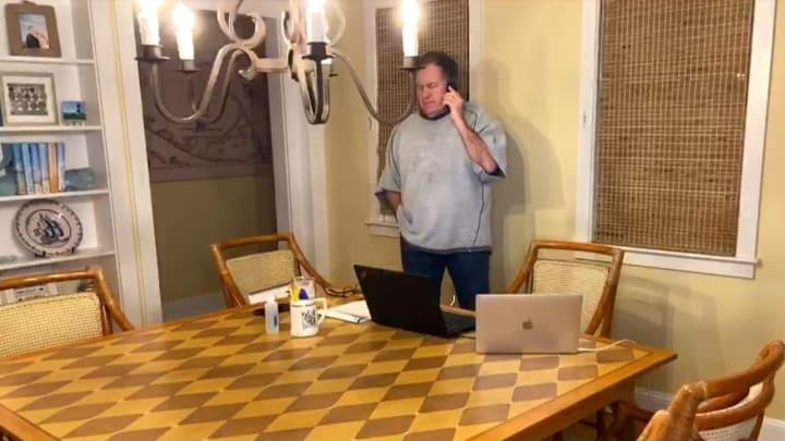 Bill Belichick drafting in a sweatshirt.