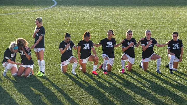 Chicago Red Stars players kneel during the national anthem.