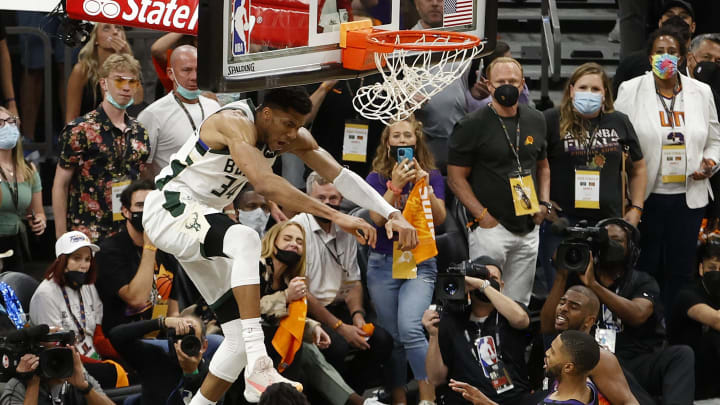Giannis finishes the alley-oop as Adele watches