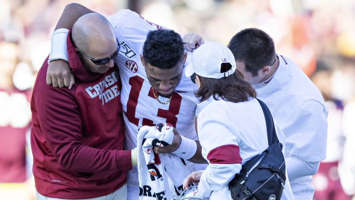 FAYETTEVILLE, AR - NOVEMBER 9:   Tua Tagovailoa #13 of the Alabama Crimson Tide is helped off the field after being injured on a play in the first half of a game against the Mississippi State Bulldogs at Davis Wade Stadium on November 16, 2019 in Starkville, Mississippi.  (Photo by Wesley Hitt/Getty Images)