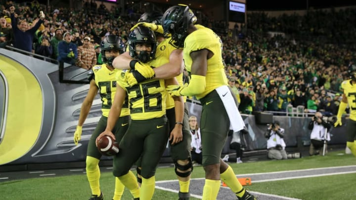 EUGENE, OREGON - NOVEMBER 16: Travis Dye #26 of the Oregon Ducks celebrates with teammates after running for a 33-yard touchdown in the fourth quarter against the Arizona Wildcats during their game at Autzen Stadium on November 16, 2019 in Eugene, Oregon. (Photo by Abbie Parr/Getty Images)