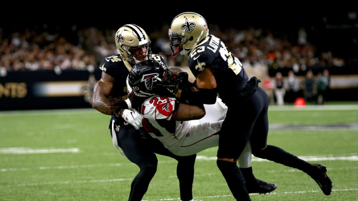 NEW ORLEANS, LOUISIANA - NOVEMBER 10: Devonta Freeman #24 of the Atlanta Falcons is tackled by Marshon Lattimore #23 of the New Orleans Saints and Vonn Bell #24 of the New Orleans Saints during a NFL game at the Mercedes Benz Superdome on November 10, 2019 in New Orleans, Louisiana. (Photo by Sean Gardner/Getty Images)
