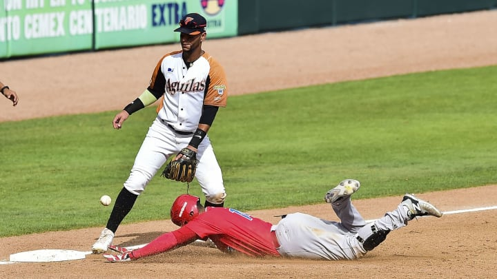Henry Ramos (R) of Criollos de Caguas of Puerto Rico slides safe in third base during the Caribbean Baseball Series match against Aguilas del Zulia of Venezuela at the Tomateros stadium in Culiacan, Sinaloa State, Mexico, on February 6, 2017. / AFP / RONALDO SCHEMIDT        (Photo credit should read RONALDO SCHEMIDT/AFP via Getty Images)