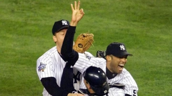 New York Yankees pitcher Mariano Rivera is rushed by teammates Scott Brosius (L) and Jorge Posada on the pitcher's mound after the Yankees defeated the Atlanta Braves 4-1 27 October, 1999, in game 4 of the 1999 World Series at Yankee Stadium in New York, NY. The Yankees won their 25th World series.   (ELECTRONIC IMAGE)  AFP PHOTO/Don EMMERT (Photo by Don EMMERT / AFP)        (Photo credit should read DON EMMERT/AFP via Getty Images)