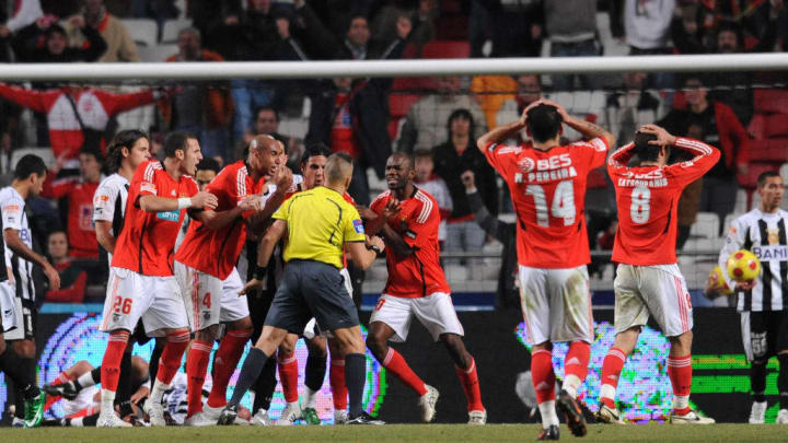 Benfica's players react to a referee's d