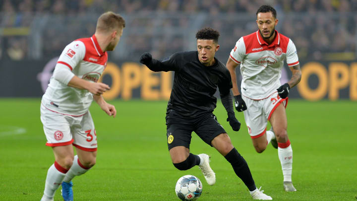 Borussia Dortmund winger Jadon Sancho dribbling against a couple of Fortuna Duesseldorf defenders.