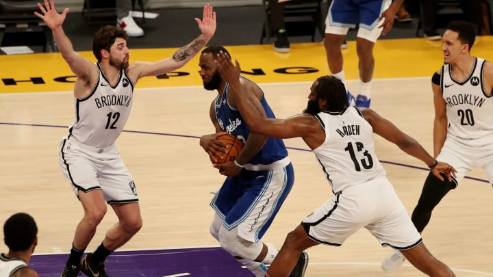 LeBron James takes the ball to the basket against James Harden and the Nets.