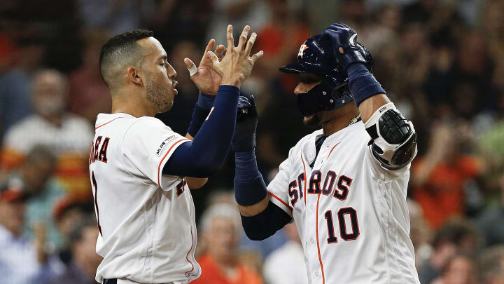 HOUSTON, TEXAS - MAY 21: Yuli Gurriel #10 and Carlos Correa #1 of the Houston Astros celebrate after Gurriel's solo home run in the fourth inning against the Chicago White Sox at Minute Maid Park on May 21, 2019 in Houston, Texas. (Photo by Bob Levey/Getty Images)