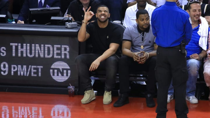 TORONTO, ON - MAY 23:  Rapper Drake reacts while sitting courtside in the first half of game four of the Eastern Conference Finals between the Cleveland Cavaliers and the Toronto Raptors during the 2016 NBA Playoffs at the Air Canada Centre on May 23, 2016 in Toronto, Ontario, Canada. NOTE TO USER: User expressly acknowledges and agrees that, by downloading and or using this photograph, User is consenting to the terms and conditions of the Getty Images License Agreement.  (Photo by Vaughn Ridley/Getty Images)