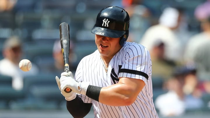 NEW YORK, NEW YORK - JULY 20:  Luke Voit #45 of the New York Yankees is hit in the mouth with a pitch in the fourth inning against the Colorado Rockies at Yankee Stadium on July 20, 2019 in New York City. (Photo by Mike Stobe/Getty Images)